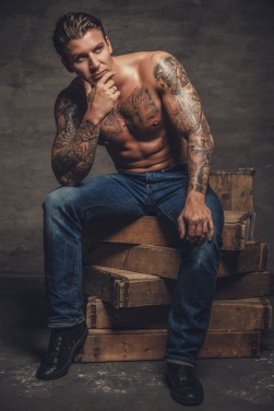 Shirtless muscular man with tattooes on his body.