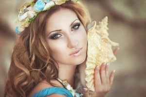 Beautiful woman mermaid with fantasy makeup in wreath