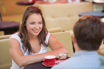 Young man and woman drinking coffee outdoor and having a chat